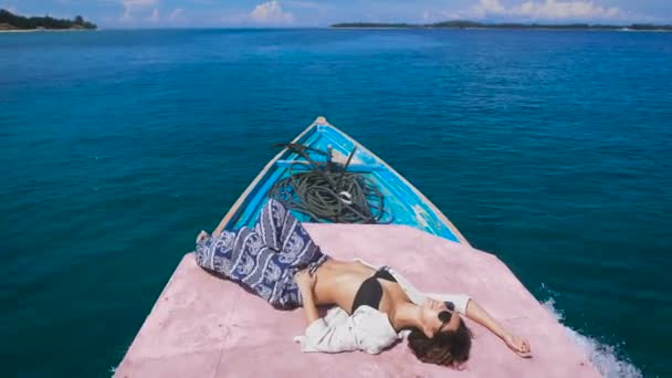 Opálená mladá dívka v sluneční brýle s hozený zpět paže za hlavu je v zádi člunu, který rychle jede na tmavě modrý oceán na malý ostrov