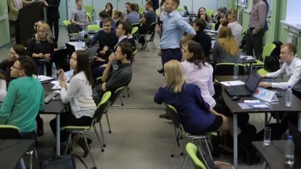 Mnoho lidí v místnosti, seděli u stolů a slance, teambuilding. Muži a ženy v místnosti jsou manažeři jedné společnosti a zahrnující v zajímavé