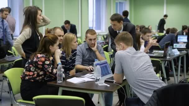 Budoucí manažeři diskutovat a analyzovat informace na obrazovce přenosného počítače na velkém sále. Během školení obchodní žádné praktické úkoly