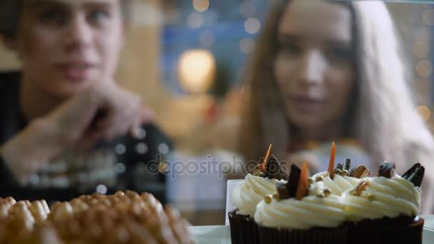 Nádherný pár mladých lidí v cukrárně. Holka a kluk v svetru vybrat dort a zákusky pro sebe. Vitrína, příjemně zařízené. Dívka s dlouhými vlasy, bruneta
