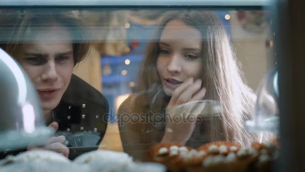 Nádherný pár mladých lidí v cukrárně. Dívka a kluk, zvolené dort a zákusky pro sebe. Vitrína, příjemně zařízený