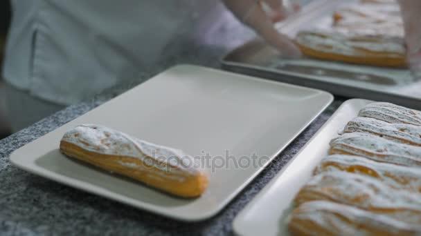 Baker által szépen összekulcsolt kézzel, frissen sült eclairs cukor por egy gyönyörű fehér lemezek, a konyhában a pékségben. Az asztalra a sok finom süteményeket.