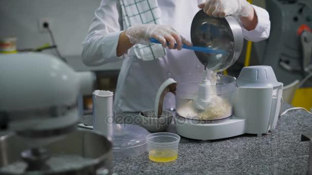 A konyhában egy édességbolt nő előkészíti a desszert. A lány kesztyű macaron készül. A munkavállaló fehér formában egészíti ki egy tálba, a proseeny lisztet, porcukrot