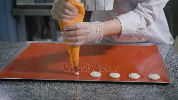 Pastelería con jeringa de repostería hace galletas del mismo tamaño ...