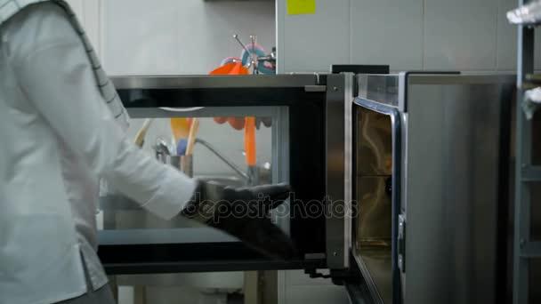 Šéfkuchař v bílé uniformě otevírá dveře trouby vytáhne zásobník čerstvě upečené rohlíky. Příprava chutné pečivo na kuchyň restaurace