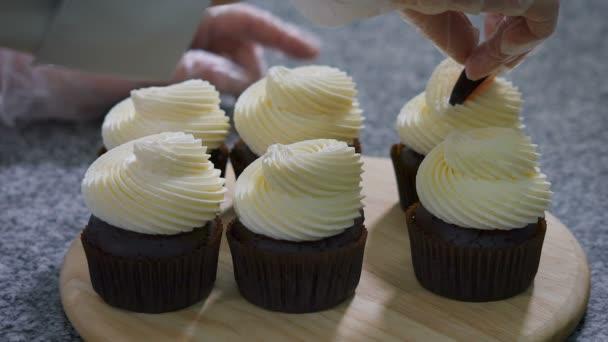 Pasticceria del cuoco unico in speciali guanti bianchi per ligiene, decorare lentamente pezzi di frutta preparata cupcakes al cioccolato con crema al burro bianco