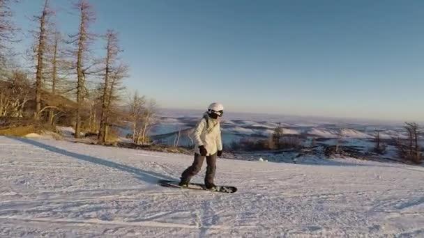 Snowboardista je sjezd na horském svahu na lyžařské středisko dnem sunny frost. Dívka v lyžařské oblečení a helmy se rychle jede z kopce, s zasněžené kopce a stromy v pozadí