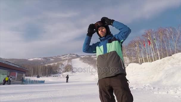 Profesionální snowboardista chystá ještě jednou sjet na horu vysokou rychlostí. Mladý muž nosí speciální brýle pro zimní sporty a dívá se jinam