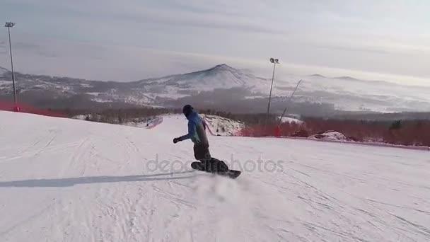 Zadní pohled mladého snowboarďáka rychle sjíždění svahu na lyžařské středisko ve vysokých horách na slunečný den. Muž v lyžařské oblečení a helmu igoing sjezdové sněhem pokrytých hill a před ním