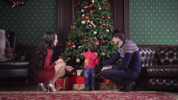 Mladá rodina sedí bohaté vánoční stromeček. Je zdobený věnec, hračky, stuhy, mašle. Maminka, Tatínek a jejich malý syn krásně oblečen do slavnostní oblečení. V pozadí, bohatý interiér