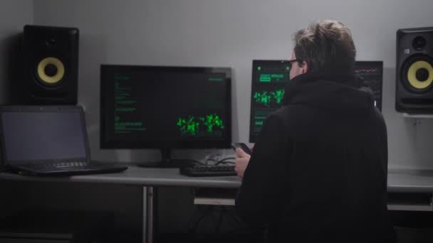 Zadní pohled na muže, který seděl u stolu pomocí svého mobilního telefonu. Cyber špionážní hacking počítačový systém s pomocí svého mobilního telefonu. Hacker snaží hesla a získat neoprávněný přístup k datům