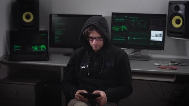 Zblízka s kapucí hacker vydělat cyberattack na síti s pomocí tabletu ve svých rukou. Člověk píše rychle, na jeho miniaplikaci a cesty zpět zobrazíte proces hacking systém na obrazovkách za