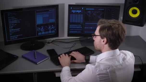 Oldalnézetből egy fiatal szabadúszó öltözve, fehér inget és smartwatch dolgozik Pc otthon. Független programozó ül előtt a számítógép-monitorok az asztalnál, és gépelés-ra billentyűzet