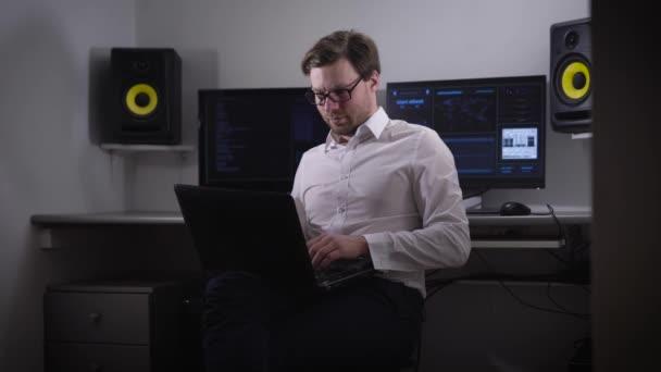 Computer in den Raum. die Person mit den Punkten und dem Laptop auf der Hand, versucht, die notwendigen Informationen zu finden. der Geek gibt Bystry-Daten in den Laptop ein, der Kerl ist sehr konzentriert