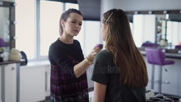 Vizážista, který pracuje v ateliéru, jistý nadace zabývá pomocí profesionální houba na tváři tichý model dlouhé kaštanové vlasy, které odstraněny svorky, aby jej v obličeji