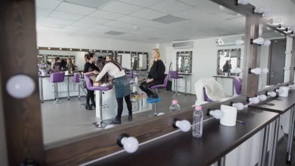 Interiér Luxusní salon krásy v moderním stylu ukázal z neobvyklého úhlu. Masters a klienti studia se odráží v zrcadle se svítilnami během jejich spolupráce