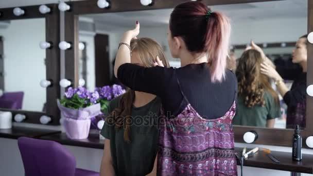 Ženské vizážista a kadeřník luxusní kosmetický salon pracuje s mladým modelem. Master je příprava na hairdoing a barvení, kontrola klientů vlasy