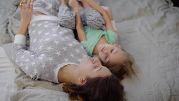 Moeder met een dochter in een slaapkamer het meisje met het kind