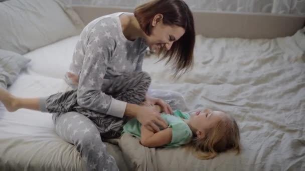Šťastná rodina hrát a objímání v posteli doma. Starší sestra žertem otřásá její maličký a oni oba rozesmálo.