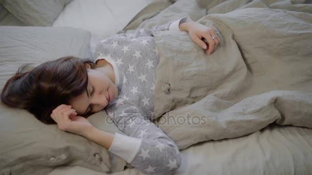 Portré, fiatal, barna nő öltözve szürke pizsama alszik az ágyban, és fekvő borított ágynemű otthon. Gyönyörű lány felébred reggel, nyúlik, és mosolyogva az új nap.