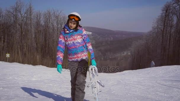 Porträt eines jungen, glücklichen Mädchens mit einem Snowboard in der Hand. Sonniger Wintertag, rund um den Berg, Skigebiet. eine Frau mit Helm, Brille, Skiausrüstung