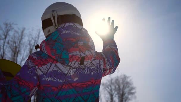 Légköri keret, a koncepció az álmok és az öröm, a nap. Egy snowboardos lány elkap a fényes nap a kezét. Egy tiszta téli napon, a hegyekben