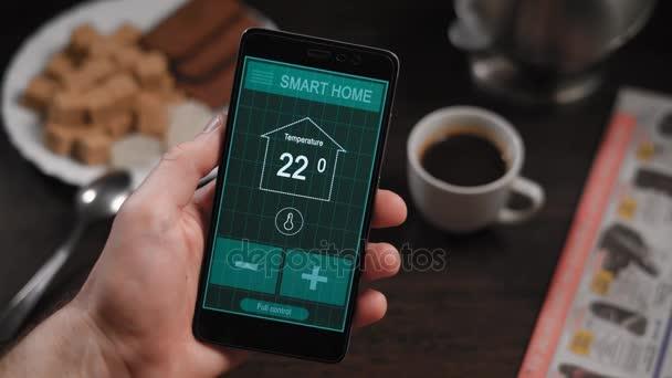 Chytré domácí, aplikace v telefonu. Muž řídí různé parametry svého domu od smartphone. Chytré domácí technologie umožňují řídit osvětlení, teplota, bezpečnostní systémy