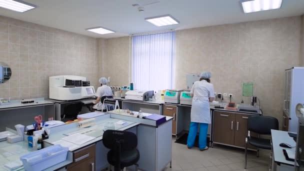 Labor mit Menschen arbeiten. Innen Schuss des klinischen Labors mit verschiedenen Geräten und Spezialisten arbeiten.