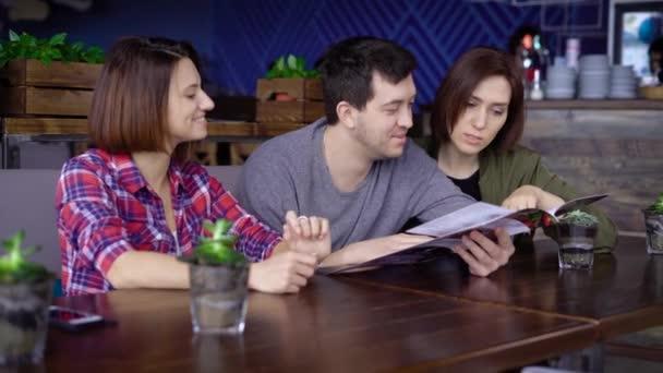 Tři usmívající se lidé sedí v kavárně a výběru potravin a nápojů na menu Brňáky. Přátelé spolu tráví čas v restauraci a diskusi o jejich stravování