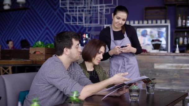 f8f7c68e61bcc3 Junge lächelnde Kellnerin im Café neben dem Tisch des Brautpaares stehen  und setzen ihre Bestellung in digital-Tablette. Mann und Frau im Restaurant  sind ...
