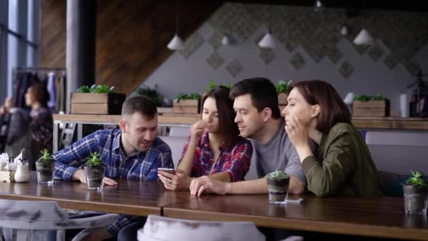 Group of four friends sitting at the restaurant together and using digital gadget. Two handsome men and two smiling women looking at the camera and making selfie photo.