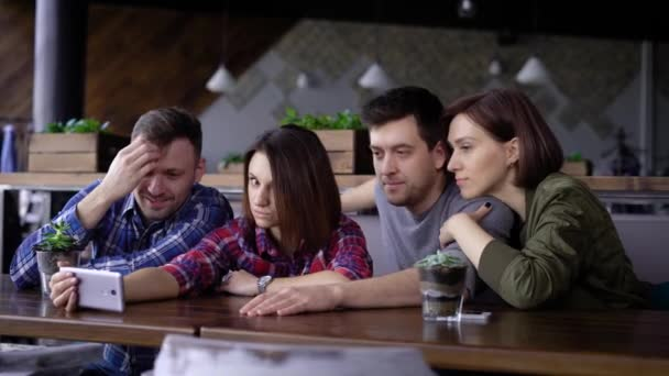 Friends sitting at the restaurant together and using digital smartphone. Two handsome men and two smiling women looking at the screen, discussing video, dancing and smiling.