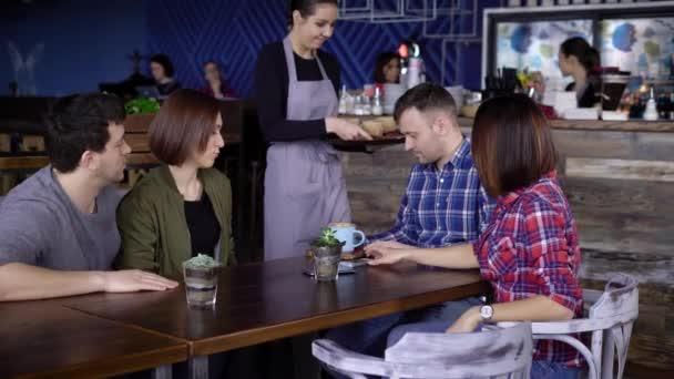 2b62057a7a20bf Vier Freunde sitzen im Restaurant verbringen ihre Freizeit zusammen und  bekommen ihre Bestellung– Stock-Filmmaterial. Gastfreundliche junge  Kellnerin ...