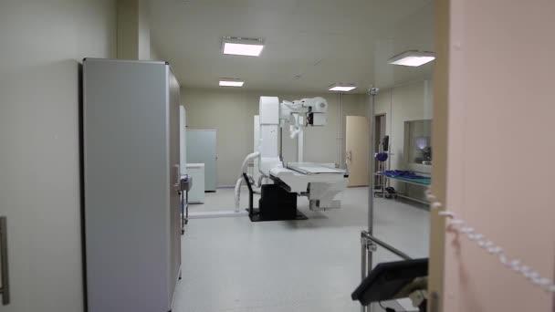 Obrázek prázdné čisté sterilní rentgenové kabinetu s moderní lékařské vybavení, zelené couch a velké radiographical zařízení v centru místnosti