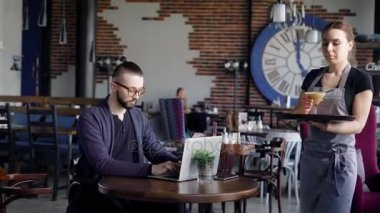 Hospitable young waitress at the cafe is bringing glass of coffee to client. Young stylish man in casual clothes is sitting at the restaurant, spending free time and working with laptop.