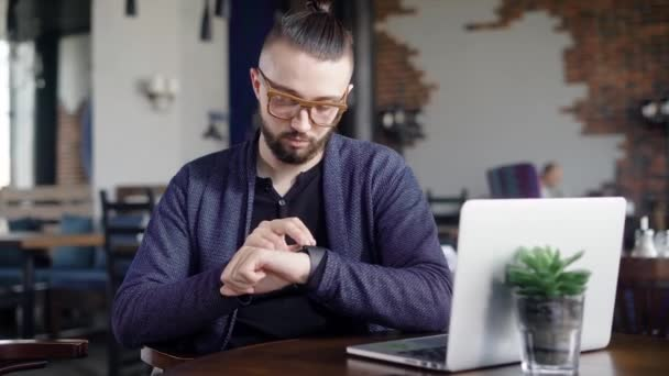 Close up of bearded hipster sitting in restaurant, looking and touching smartwatch. Male designer is waiting for client at the table in cafeteria with laptop and modern wristwatch on his hand.