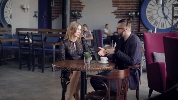 Pohostinný mladá servírka přináší nápoj v hnědý keramický hrnek do tabulky pro ženu. Pár sedí v restauraci a mluví. Kolegové s přestávka na kávu v kavárně