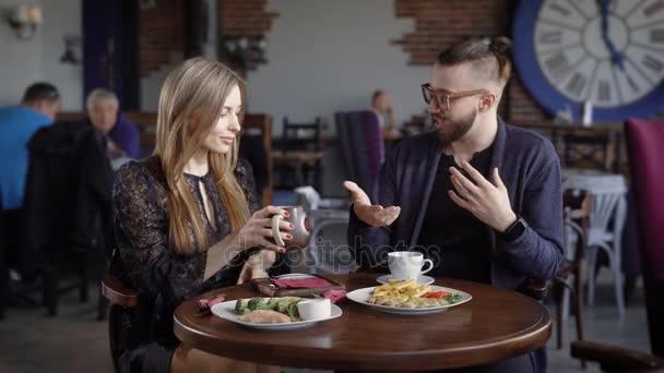 Šťastný pár muž a žena sedí v kavárně stolu servírované s potravin a nápojů spolu trávili čas. Krásná dáma pití kávy poslouchal její rozkládali přítele.