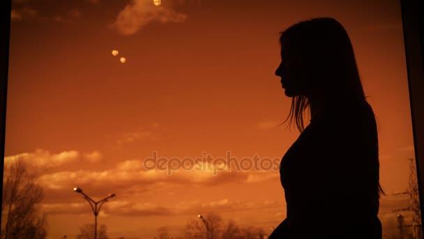 Sötét sziluettje egy nő, áll a profil a twilight backcloth az ablak mellett. Vázlat a női test ellen narancssárga naplemente ég, fehér felhők és a fák, a háttérben.