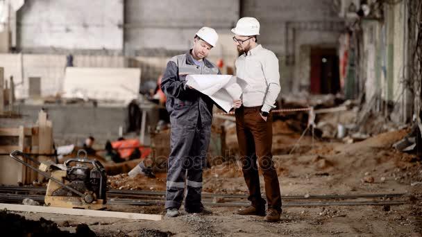 Inženýr ukazuje zákazníka v ochranné přilbě odhad nové budovy za účelem změny jeho rekonstrukce