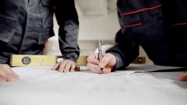 Zblízka střílet na stavitelé rukou, který provede opravy na papírech stavebních výkresů, aby to byla pravda, aby