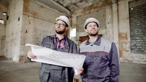 Dva muži, kteří tvůrci v ochrannou přilbu na jejich hlavy a zvláštní oblečení podívat na tovární budova k rekonstrukci
