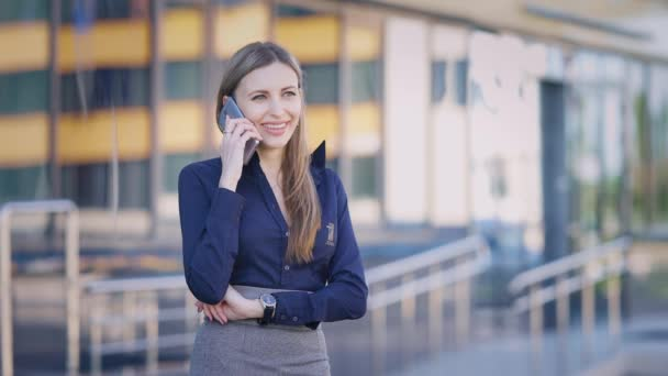eine geschäftstüchtige Dame telefoniert während ihrer Arbeitspause mit ihrem Handy, die Dame spricht mit einer Kollegin in der Nähe des Bürogebäudes
