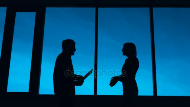 Silueta natáčení ženy a muže, který vede dialog na pozadí windows a modrá obloha