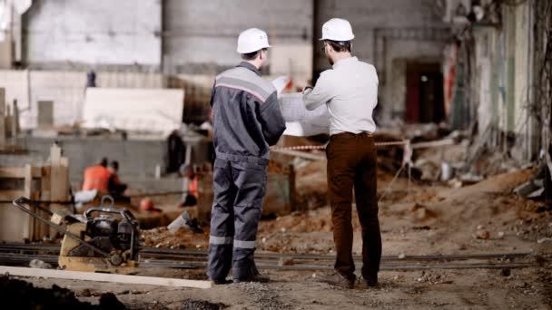 Az ipari létesítmény építése. A mester beszél, és a vezető mérnök a projekt. Férfi kommunikálni.