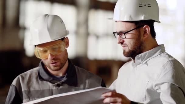 Hlavní inženýr a mistr stavby v průmyslovém zařízení. Inženýr se dívá na plán a diskutuje s hlavní předák na staveništi