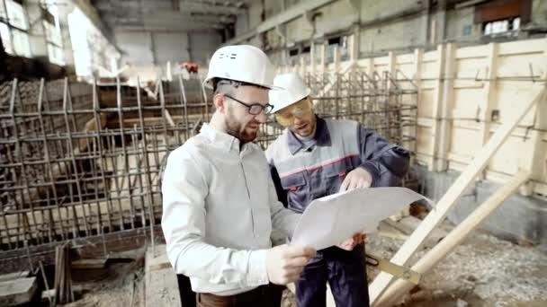 Architekt a hlavní předák na staveništi elektrárny. Muži hovoří o nedostatky ve výkresu. Na pozadí stavební práce