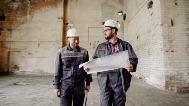 Dělník a foreman na staveništi dílny. Stavitel oblečený v speciální uniformě a s helmou na jeho hlavu ukazuje práci předák.