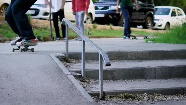 Zavřete a pak vystřelí skateboardisty noh, který provádí klouzání na palubě podél schodiště zábradlí směrem dopředu v době letních
