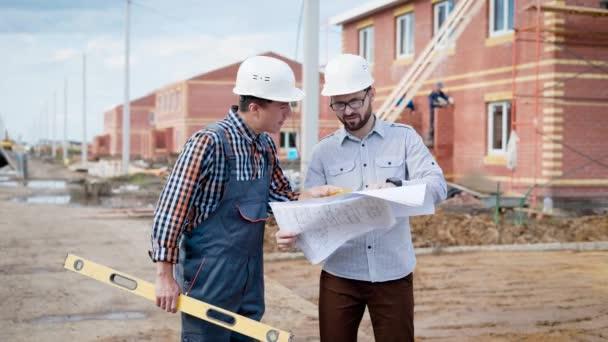 Bauarbeiterteam bei der Arbeit. Polier und Baumeister mit Bauniveau